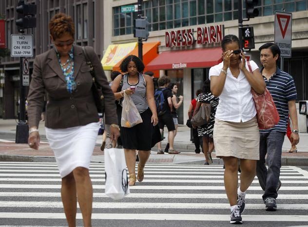 Pedestrians cross K Street and Connecticut Avenue near the Farragut North Metro entrance in Northwest Washington on July 10, 2012. (Associated Press)