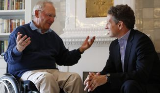 German Finance Minister Wolfgang Schaeuble (left) speaks July 30, 2012, with U.S. Treasury Secretary Timothy Geithner in the house where Schaeuble is vacationing, in Westerland on the North Sea island of Sylt, Germany. (Associated Press)