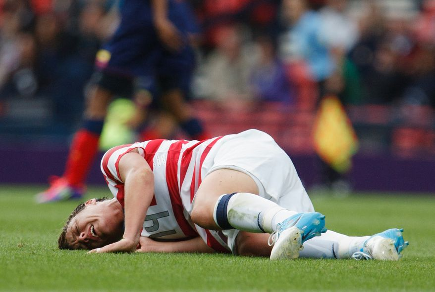 United States' Abby Wambach lays on the field after suffering from an injury at the hands of Colombia's Lady Andrade during the group G women's soccer match between the United States and Colombia at the London 2012 Summer Olympics, Saturday, July 28, 2012, at Hampden Park Stadium in Glasgow, Scotland. (AP Photo/Chris Clark)