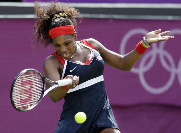 Serena Williams of the United States returns a shot to Urszula Radwanska at the All England Lawn Tennis Club at Wimbledon, in London, at the 2012 Summer Olympics, Monday, July 30, 2012. (AP Photo/Mark Humphrey)