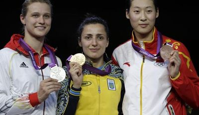 Gold medalist Ukraine's Yana Shemyakina is flanked by silver medalist Germany's Britta Heidemann, left, and bronze medalist China's Yujie Sun pose after the women's individual epee fencing gold medal match at the 2012 Summer Olympics, Monday, July 30, 2012, in London. (AP Photo/Andrew Medichini)