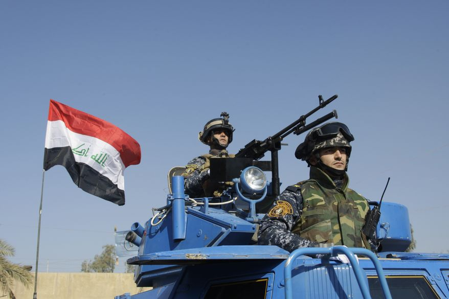 **FILE** The Iraqi flag waves Nov. 22, 2011, while federal police parade in Baghdad. (Associated Press)