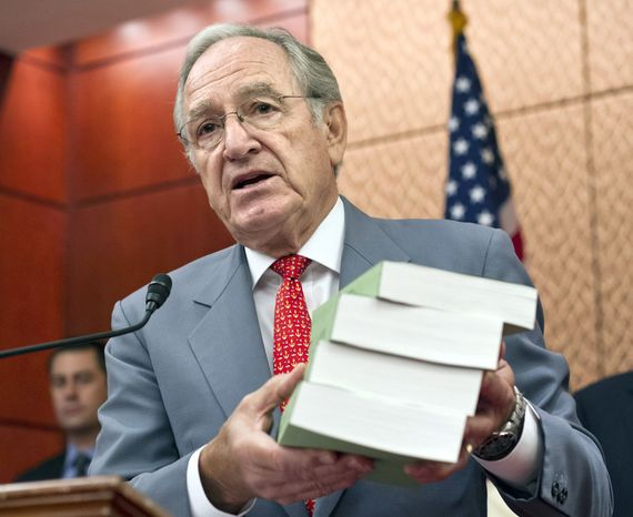 Sen. Tom Harkin, Iowa Democrat, holds the four-volume report asserting that for-profit colleges often hit students with exorbitant tuition, aggressive recruiting and abysmal outcomes. Monday, July 30, 2012, on Capitol Hill in Washington. (Associated Press)