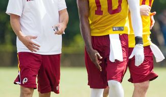 Redskins offensive coordinator Kyle Shanahan (left) and rookie quarterback Robert Griffin III talk as quarterback Rex Grossman jogs by during afternoon practice at Redskins Park in Ashburn. (Handrew Harnik/The Washington Times)