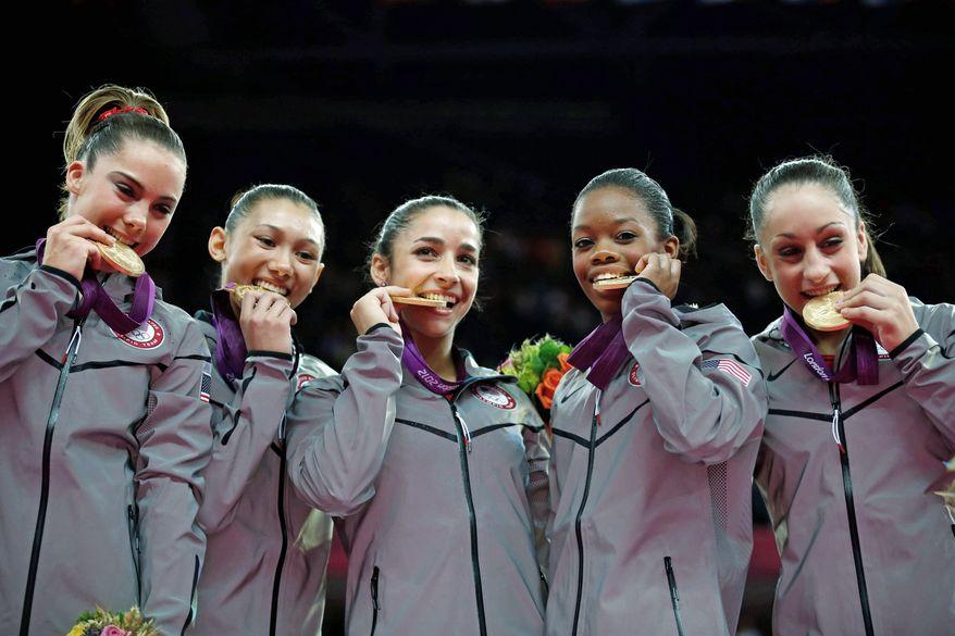 U.S. gymnasts U.S. gymnast McKayla Maroney, Kyla Ross, Alexandra Raisman, Gabrielle Douglas and Jordyn Wieber bite their gold medals at the Artistic Gymnastics women's team final at the 2012 Summer Olympics, Tuesday, July 31, 2012, in London. (AP Photo/Matt Dunham)