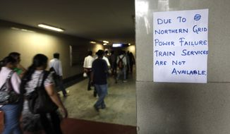 A handwritten notice about power failure is pasted outside a Metro station in New Delhi on July 31, 2012, after Delhi Metro rail services were disrupted following power outages. (Associated Press)