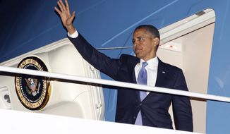 President Obama waves July 30, 2012, as he boards Air Force One before his departure from JFK International airport in New York. Obama traveled to New York for a private fundraiser. (Associated Press)