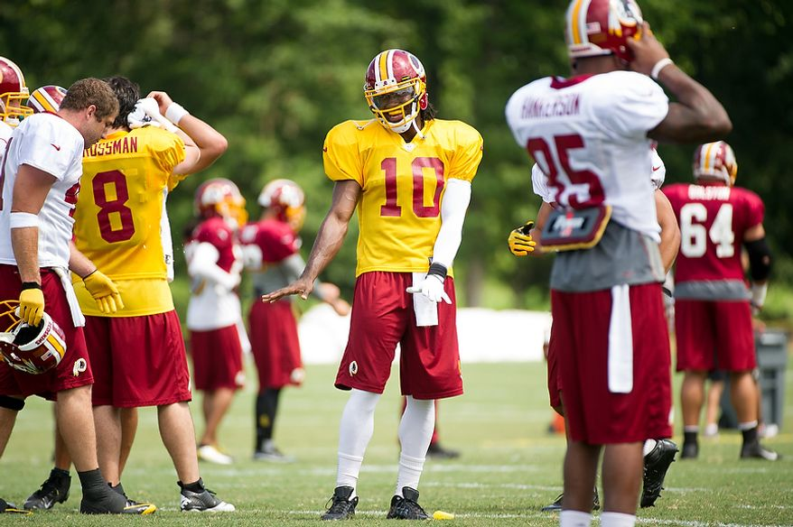 Washington Redskins quarterback Robert Griffin III (10), center, shares a laugh with teammates on the field during afternoon practice at the Washington Redskins training camp at Redskins Park, Ashburn, Va., Washington, D.C., Monday, July 30, 2012. (Andrew Harnik/The Washington Times)