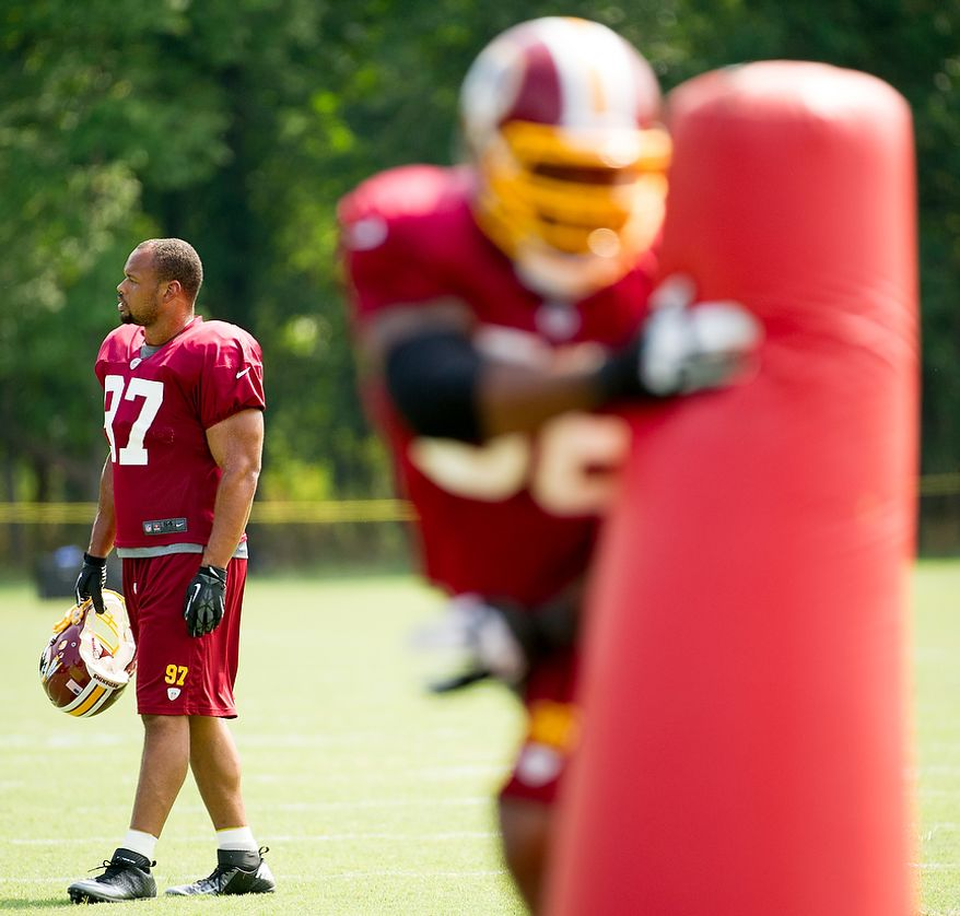 Washington Redskins linebacker Lorenzo Alexander (97), left, takes a break during afternoon practice at the Washington Redskins training camp at Redskins Park, Ashburn, Va., Washington, D.C., Monday, July 30, 2012. (Andrew Harnik/The Washington Times)