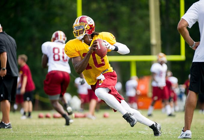 Washington Redskins quarterback Robert Griffin III (10) rolls out to his left during afternoon practice at the Washington Redskins training camp at Redskins Park, Ashburn, Va., Washington, D.C., Monday, July 30, 2012. (Andrew Harnik/The Washington Times)