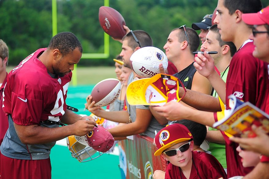 Lorenzo Alexander (#97) signs autographs for fans during Redskins' training camp at Redskins Park, Ashburn, Va., Monday, July 30, 2012.  (Ryan M.L. Young/The Washington Times)
