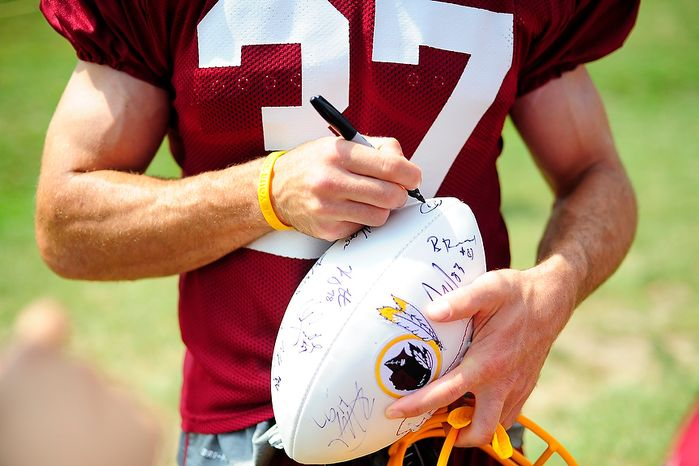 Reed Doughty (#37) signs an autograph for a fan during Redskins' training camp at Redskins Park, Ashburn, Va., Monday, July 30, 2012.  (Ryan M.L. Young/The Washington Times)