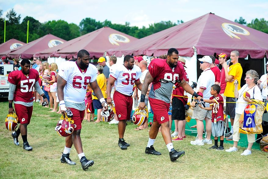 From left to right, Donnell Holt (#57), Willie Smith (#69), Darrel Young (#36), and Doug Worthington (#90) take the field during Redskins' training camp at Redskins Park, Ashburn, Va., Monday, July 30, 2012.  (Ryan M.L. Young/The Washington Times)