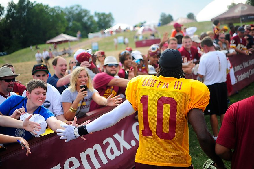 Robert Griffin III gives fans high fives as he runs by following afternoon workouts at Redskins' training camp at Redskins Park, Ashburn, Va., Monday, July 30, 2012.  (Ryan M.L. Young/The Washington Times)