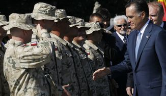 Republican presidential candidate and former Massachusetts Gov. Mitt Romney meets Polish veterans from the Iraq and Afghanistan wars as he visits the Tomb of the Unknown Soldier in Warsaw, Poland, Tuesday, July 31, 2012. (AP Photo/Charles Dharapak)