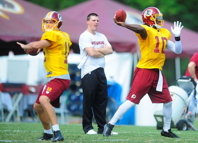 Ryan M.L. Young/The Washington Times  Redskins rookie quarterbacks Robert Griffin III (right) and Kirk Cousins honed their skills during drills this week.