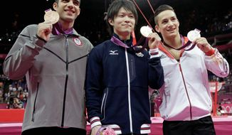 Gymnasts (from left) Danell Leyva, Kohei Uchimura and Marcel Nguyen show off their all-around medals Wednesday. Leyva, a Cuban immigrant competing for the United States, rallied to land the bronze. (Associated Press)