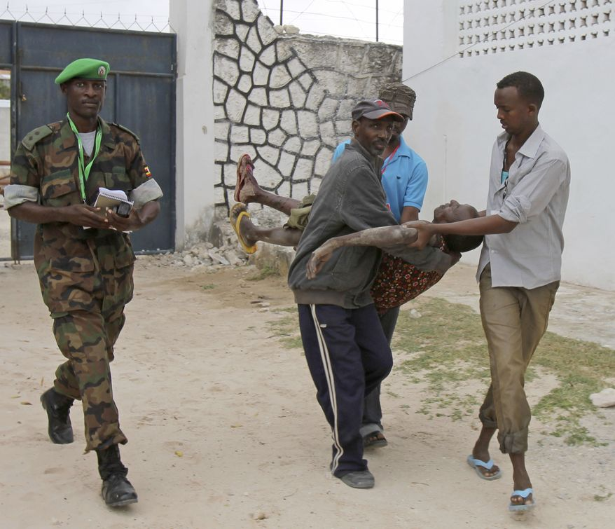 Somali police men carry an injured Somali soldier in Mogadishu on Aug.1, 2012. The soldier was injured during an attempt by two suicide bombers to blow up the constituent assembly venue, police said. The bombers were shot dead by security forces. (Associated Press)