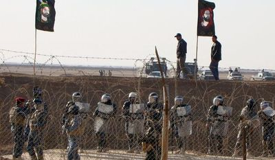 **FILE** Iraqi police stand guard outside the camp of the Mujahedeen-e-Khalq (MEK), also known as the People's Mujahedeen Organization of Iran, northeast of Baghdad on Dec. 9, 2011. (Associated Press/People's Mujahedeen Organization of Iran)