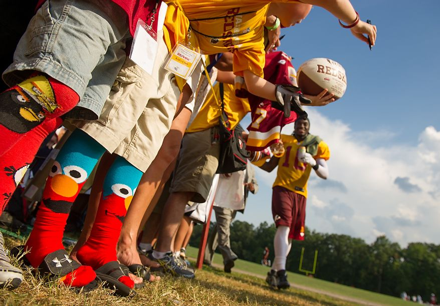 Washington Redskins fan Maguire Willard, 10, of Martinsburg, W.Va. wears long sox with Elmo sox on them as Washington Redskins quarterback Robert Griffin III (10), walks by following afternoon practice at training camp at Redskins Park, Ashburn, Va., Wednesday, August 1, 2012. Griffin has been known to wear a variety of themed socks. (Andrew Harnik/The Washington Times)