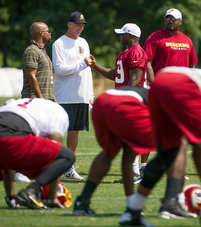 Washington Redskins defensive coordinator Jim Haslett, second from left, talks with Washington Redskins linebacker London Fletcher (59), second from right, during afternoon practice at training camp at Redskins Park, Ashburn, Va., Wednesday, August 1, 2012. (Andrew Harnik/The Washington Times)
