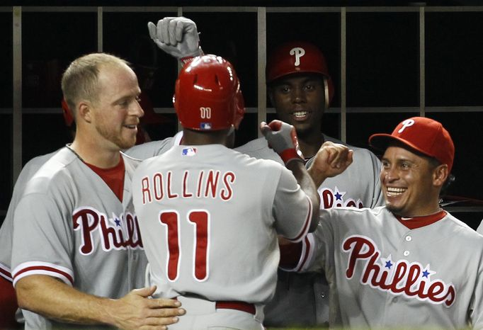 Philadelphia Phillies' Jimmy Rollins (11) celebrates with teammates in the dugout after hitting a home run in the fifth inning during a baseball game against the Philadelphia Phillies, Wednesday, Aug. 1, 2012, in Washington. The Phillies won 3-2. (AP Photo/Carolyn Kaster)