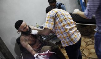 In this Wednesday, Aug. 2, 2012 photo, a Syrian medic helps a wounded man in Maarat Misrin, Idlib province, northern Syria. (AP Photo)