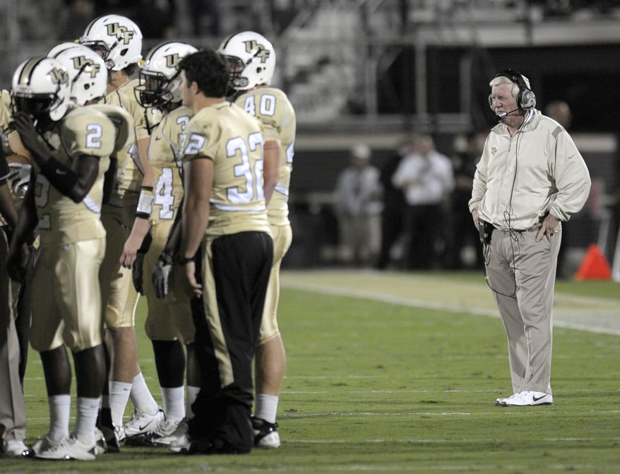 FILE - In this Nov. 25, 2011, file phot, Central Florida head coach George O'Leary, right, watches as his team huddles on the field during an NCAA college football game against UTEP in Orlando, Fla. UCF will have to sit out the postseason for a year in men's basketball and football under sanctions the NCAA handed down, Tuesday, July 31, 2012, adding to penalties the school self-imposed after major recruiting violations were uncovered last year in both programs. Former athletics director Keith Tribble and assistant football coach David Kelly were cited for unethical conduct by the NCAA last year and resigned. Basketball coach Donnie Jones served a three-game suspension last season.  (AP Photo/Phelan M. Ebenhack, File)