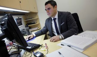 ** FILE ** In this Wednesday, Aug. 1, 2012, photo, New York Stock Exchange Senior Compliance Associate Matthew Pizzo, an Air Force veteran who has law and business degrees, works in his office at the New York Stock Exchange. Pizzo had gone two years without work, until recently, as he is now finishing his first week of work at the exchange. U.S. employers added 163,000 jobs in July, a hopeful sign after three months of sluggish hiring. (AP Photo/Richard Drew)