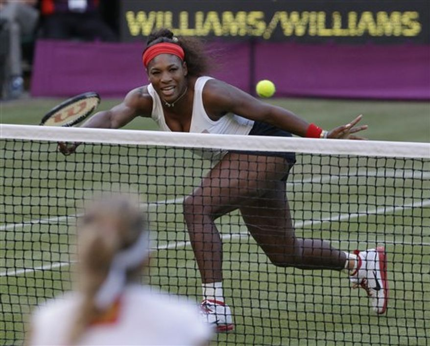 Serena Williams of the United States volleys against Maria Kirilenko, below, of Russia in their women's doubles semifinal match at the All England Lawn Tennis Club in Wimbledon, London at the 2012 Summer Olympics, Saturday, Aug. 4, 2012. (AP Photo/Elise Amendola)