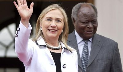 U.S. Secretary of State Hillary Rodham Clinton, left, waves to the media after meeting with Kenya President Mwai Kibaki at the State House, in Nairobi, Kenya, on Saturday, Aug. 4, 2012. (AP Photo/Jacquelyn Martin, Pool)