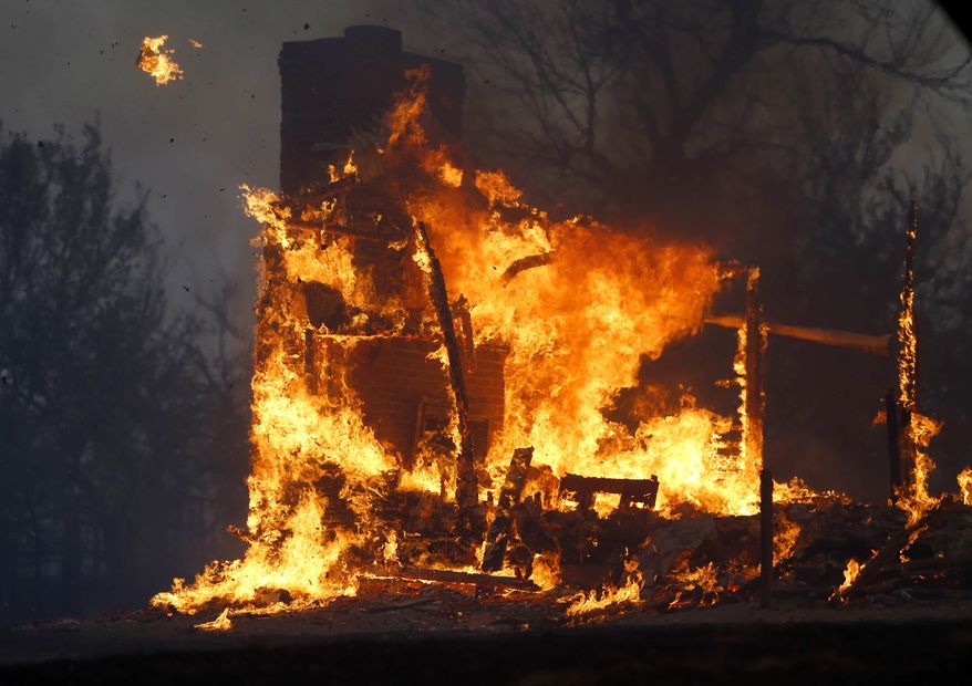 A home burns during a large wildfire Friday, Aug. 3, 2012, in Luther, Okla. A wildfire whipped by gusty, southerly winds swept through rural woodlands north and south of Oklahoma City on Friday, burning several homes as firefighters struggled to contain it in 113-degree heat. (AP Photo/The Oklahoman, Bryan Terry)