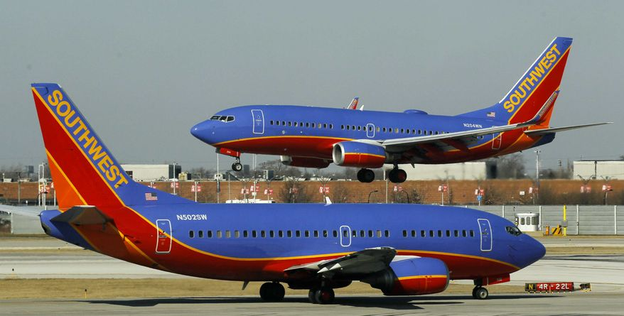 ** FILE ** In this Feb. 9, 2012, file photo, a Southwest Airlines Boeing 737 waits to take off at Chicago's Midway Airport as another lands. (AP Photo/Charles Rex Arbogast, File)