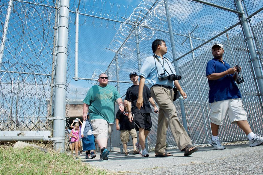 People walk through a gated area to enter the Maryland House of Correction in Jessup, Md., during an open house Sunday. The prison was built in 1879 and closed in 2007 after the deaths of two correctional officers. (Barbara L. Salisbury/The Washington Times)