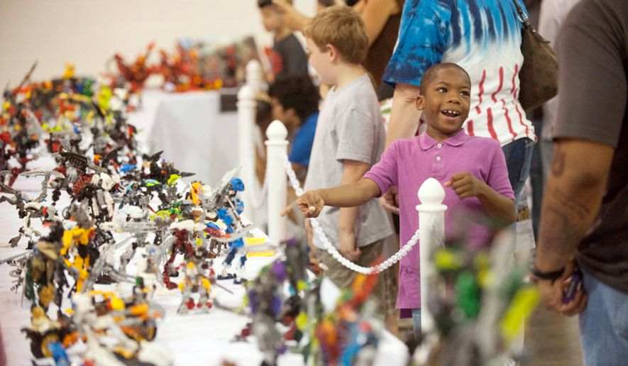 Dallas Washington, 7, from Washington, D.C., points at a Lego display during the Brickfair Lego Convention. (Raymond Thompson/The Washington Times)