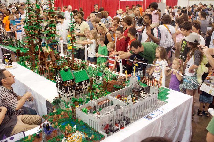 Spectators examine a castle built of lego during the Brickfair Lego Convention.  (Raymond Thompson/The Washington Times)