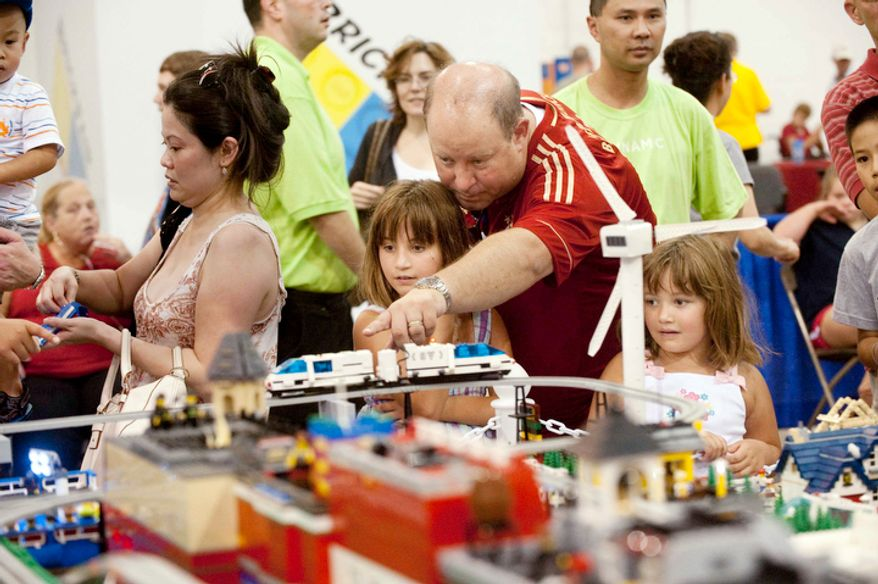 **FILE** Mark Schwender of Springfield, Va., points out details on the Studsville display to his daughters Stephanie, 8, and Valerie, 5, during the Brickfair Lego Convention at the Dulles Expo Center on Aug. 5, 2012, in Chantilly. (Raymond Thompson/The Washington Times)