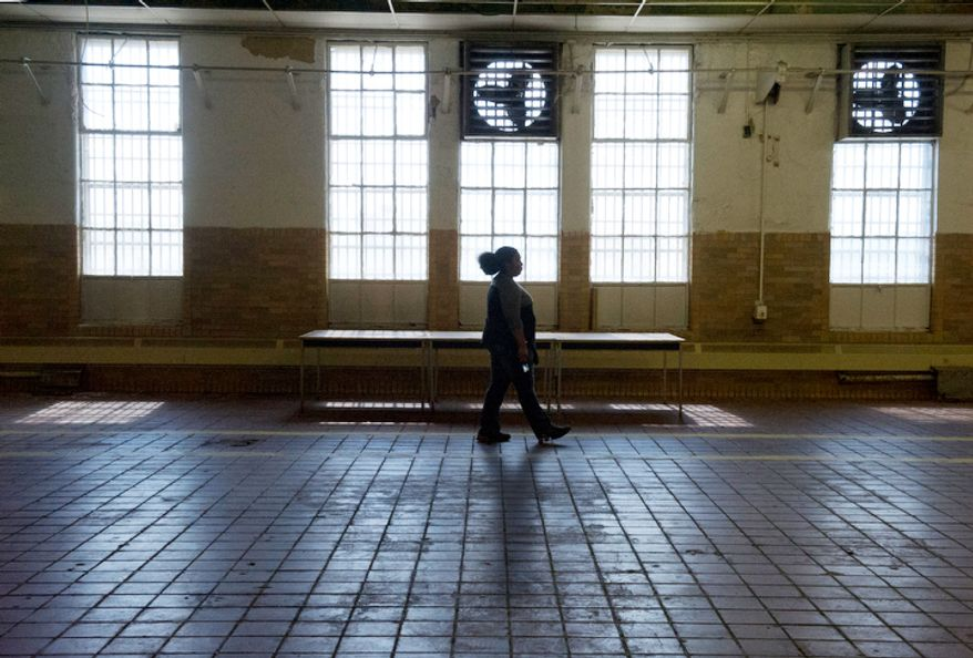 A woman walks through the now-empty mess hall at the Maryland House of Corrections Later this year the prison will actually be deconstructed brick by brick by inmates, and some parts will be reused in other institutions. (Barbara L. Salisbury/The Washington Times)