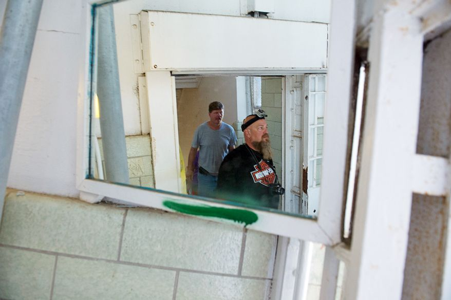 People touring the Maryland House of Corrections are seen reflected in a mirror as they make their way into a day room outside of one of the dormitories. (Barbara L. Salisbury/The Washington Times)