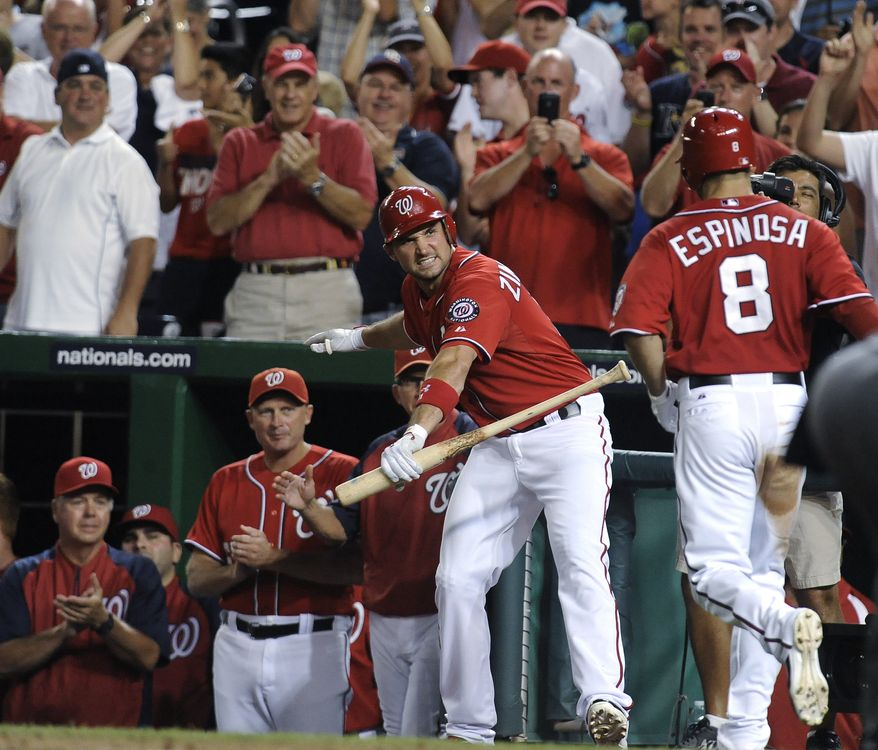 Washington Nationals' Ryan Zimmerman, center, awaits the arrival of teammate Danny Espinosa (8) after Espinosa hit a three-run home run in the eighth inning of a baseball game against the Florida Marlins at Nationals Park, Saturday, Aug. 4, 2012, in Washington. The Nationals won 10-7. (AP Photo/Richard Lipski)