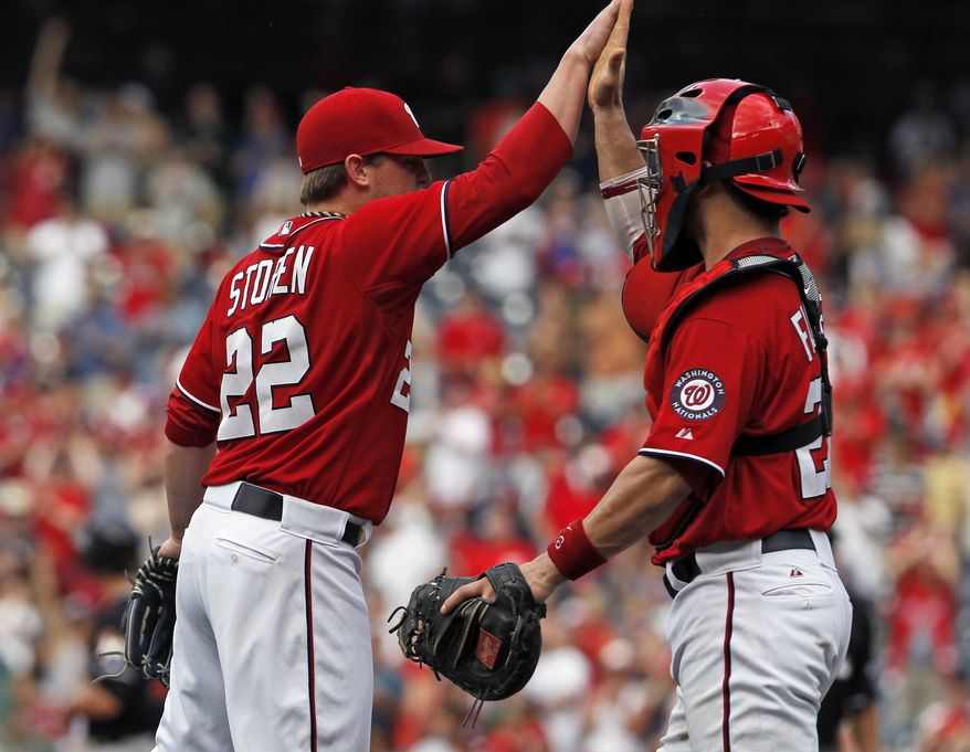 Washington Nationals relief pitcher Drew Storen, left, reacts with catcher Jesus Flores after a baseball game with the Miami Marlins, Sunday, Aug. 5, 2012, in Washington. The Nationals won 4-1. (AP Photo/Alex Brandon)