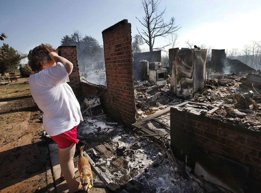 Rebecca Kolar stands at the entrance to the three bedroom, brick home at 908 S. Dogwood St. where she and her husband, Douglas, lived with their two children for 13 years before fire destroyed it, Saturday, Aug. 4, 2012, in Luther, Okla. (AP Photo/The Oklahoman, Jim Beckel)