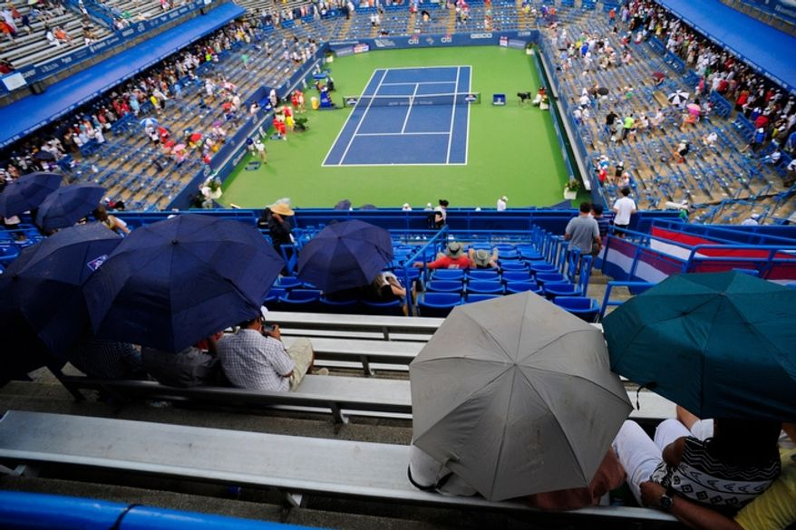 Spectators wait out the rain during the men's finals match between Tommy Haas and Alexandr Dolgopolov at the Citi Open tennis tournament at the William H.G. FitzGerald Tennis Center, Washington D.C., Sunday, August 5, 2012.  The match has been delayed several times due to rain.  (Ryan M.L. Young/The Washington Times)