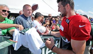 Tim Tebow greets fans who traveled to the quaint town of Cortland in central New York to see the most popular backup quarterback in the NFL. Hosting the New York Jets training camp is estimated to generate $5.8 million for the local economy, and Tebow is expected to bring a 30 percent increase in visitors. (Associated Press)