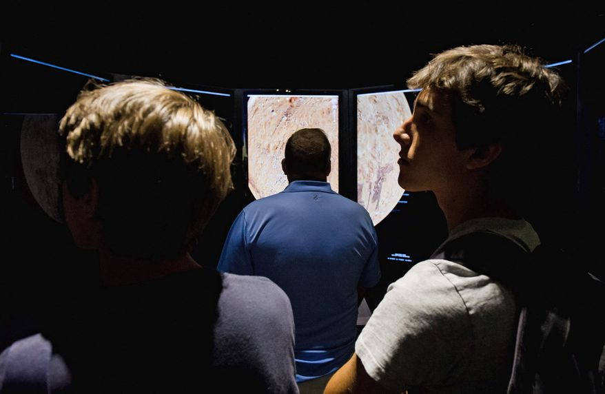 Brothers Riccardo (left), 16, and Ruggero Amaduzzi, 19, wait their turn to control a large panoramic interactive digital map of the surface of Mars at the Smithsonian National Air and Space Museum in Washington, D.C., on Monday during a NASA press conference streamed live on the landing of Curiosity. (Andrew Harnik/The Washington Times)