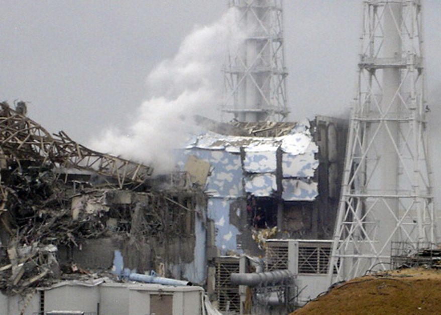 """**FILE** Smoke rises March 15, 2011, from the badly damaged Unit 3 reactor (left), next to the Unit 4 reactor covered by an outer wall at the Fukushima Dai-ichi nuclear complex in Okuma, Japan. The emergency command center at Japan's stricken nuclear plant shook violently when hydrogen exploded at Unit 3 and the plant chief reacted by shouting, """"This is serious, this is serious,"""" reveal videos of the crisis as it happened. (Associated Press/Tokyo Electric Power Co., File)"""