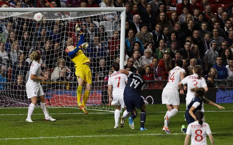 The United States' Alex Morgan, far right, scores past Canada's goalkeeper Erin Mcleod, second from left, in the final minutes of extra time in the semi-final women's soccer match between the USA and Canada in the 2012 Summer Olympics, Monday, Aug. 6, 2012, at Old Trafford in Manchester, England. (AP Photo/Ben Curtis)