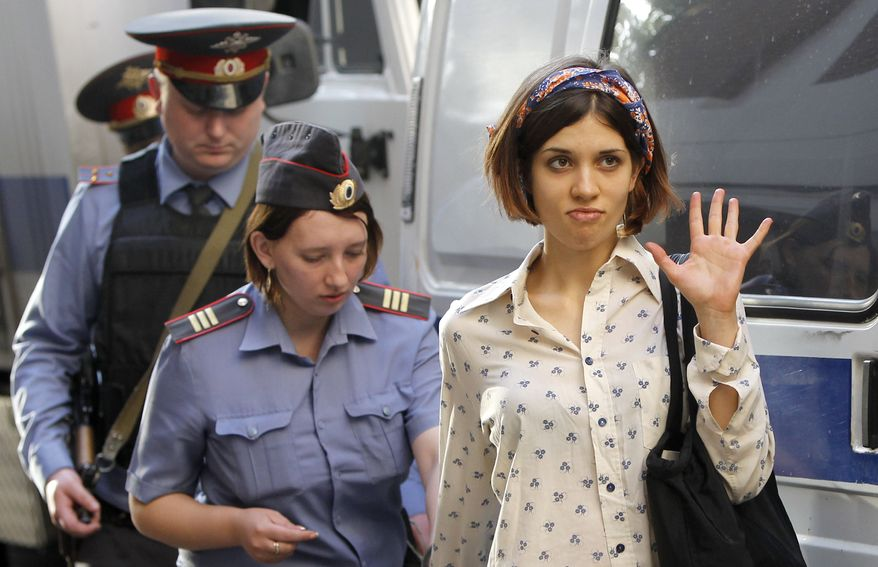 ** FILE ** Nadezhda Tolokonnikova (right), a member of feminist punk band Pussy Riot, is escorted on Wednesday, Aug. 1, 2012, to a police van in Moscow. (Associated Press)