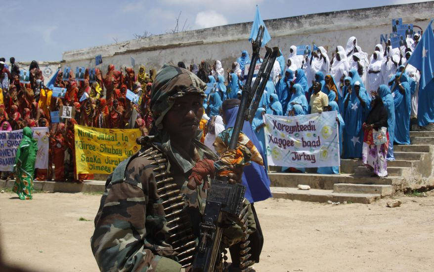 A Somali soldier stands guard Aug. 6, 2012, in Mogadishu as Somalis gather in a stadium. Somalis took to the streets to celebrate the one-year anniversary of the ouster of al Shabab militants, the culmination of years of warfare by African Union and Somali forces that has allowed Mogadishu bask in a year of relative peace. (Associated Press)