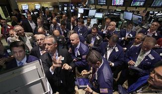 Specialist Donald Himpele, foreground second left, resumes trading in AIG stock on the floor of the New York Stock Exchange Friday, Aug. 3, 2012. The U.S. government says it plans to sell $4.5 billion in American International Group common stock, the latest effort to recoup taxpayer money spent on the largest bailout of the 2008 financial crisis. (AP Photo/Richard Drew)